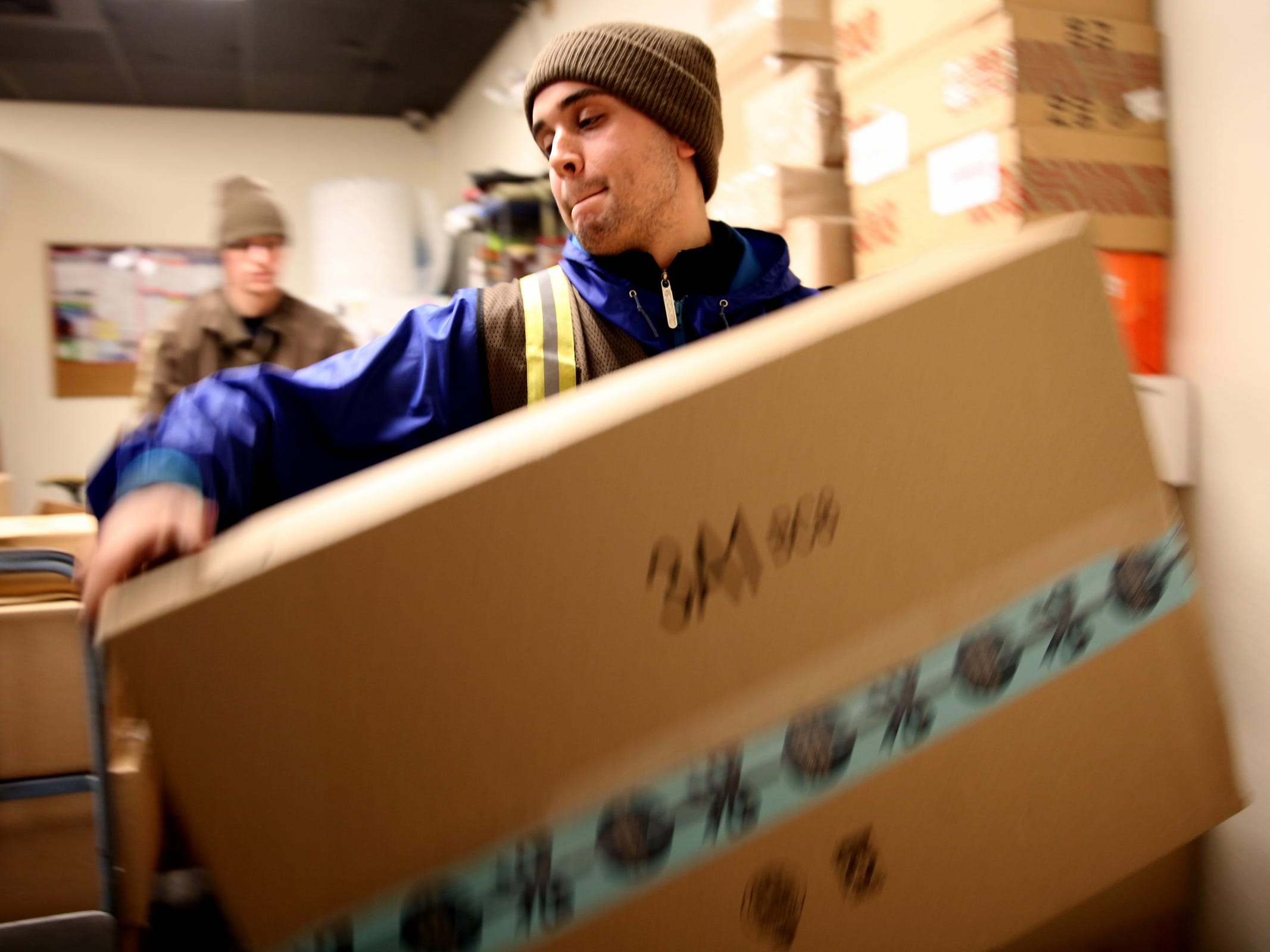 Jonnah Ferreiro, a UPS seasonal employee, grabs a package to be delivered at the UPS Store on Commercial St. SE in Salem on Tuesday, Dec. 4, 2018.