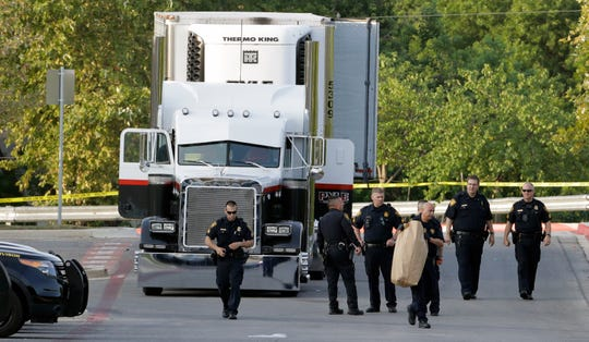 San Antonio police officers investigate the scene where eight people were found dead in a tractor-trailer loaded with at least 30 others outside a Walmart store in stifling summer heat in what police are calling a horrific human trafficking case July 23, 2017, in San Antonio.