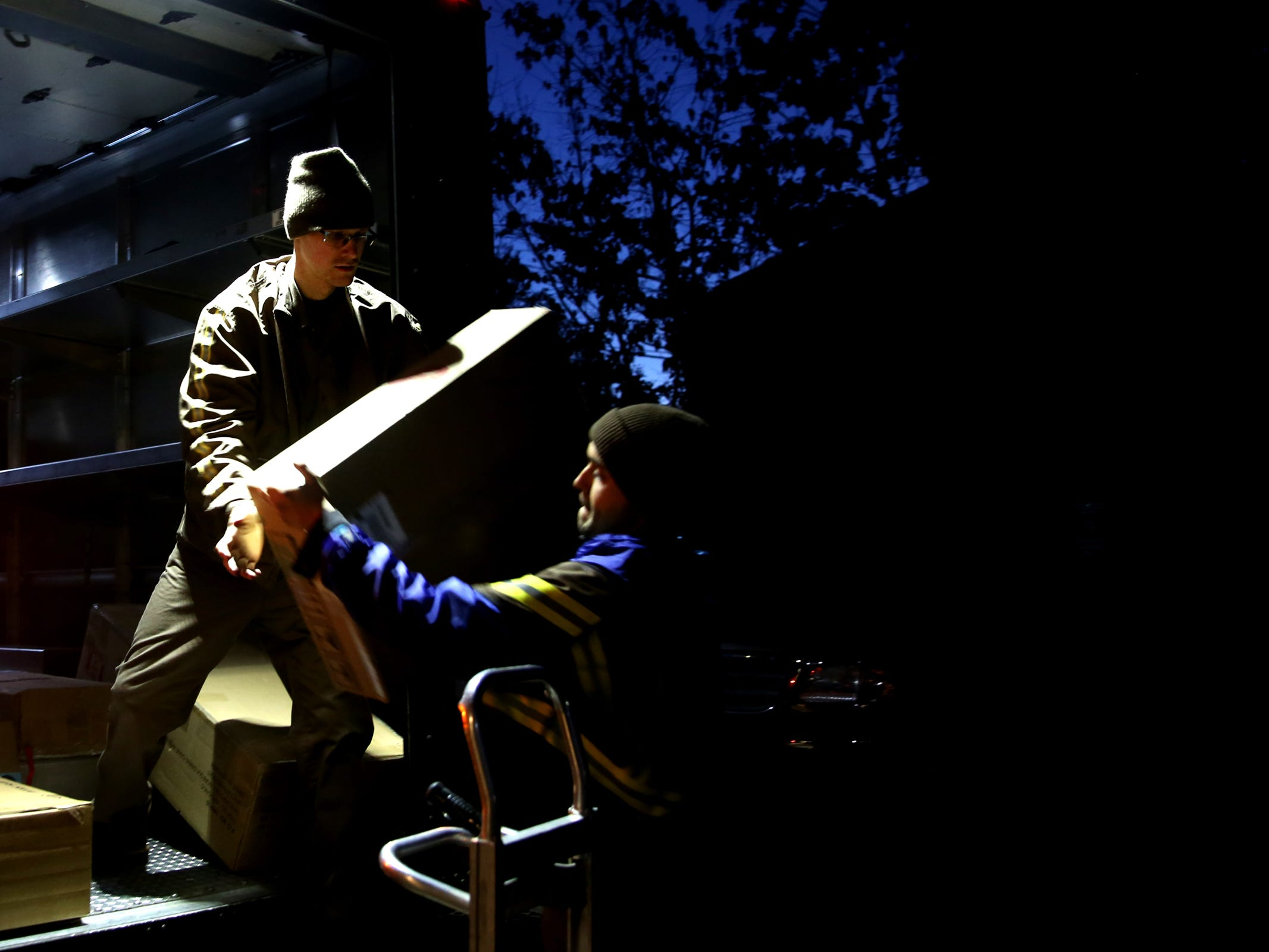 Fred Kapsoff, left, a UPS service provider, grabs a package from Jonnah Ferreiro, a seasonal employee, as they load a truck outside the UPS Store on Commercial St. SE in Salem on Tuesday, Dec. 4, 2018.