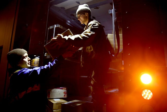 Fred Kapsoff, right, a UPS service provider, grabs a package from Jonnah Ferreiro, a seasonal employee, as they load a truck outside the UPS Store on Commercial St. SE in Salem on Tuesday, Dec. 4, 2018.