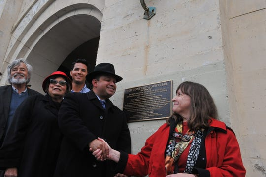Supervisor Luis Alejo shakes hands with Nancy Runyon, president of the Alliance of Monterey Area Preservationists, to celebrate the Old Monterey County Jail plaque commemoration.