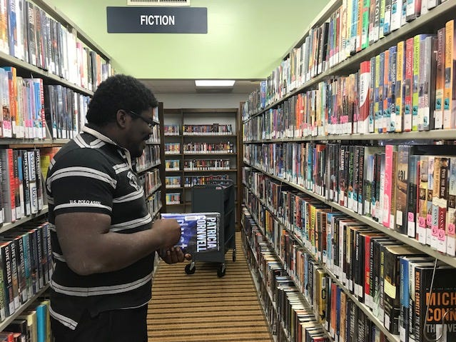 Librarian assistant Cayddrick Ballard sorting books at the Tom Green County Library North Angelo Branch, 3001 N. Chadbourne St.