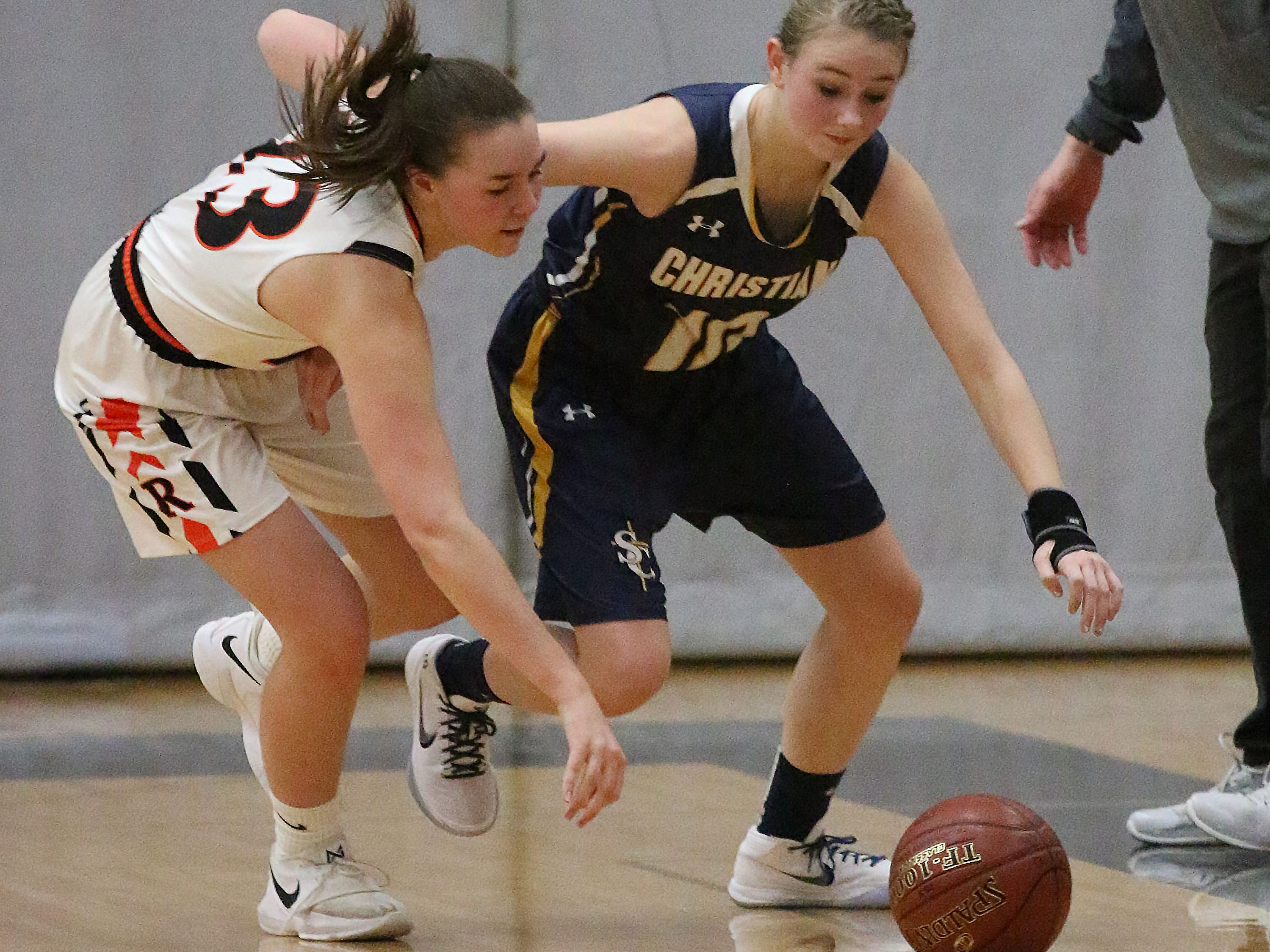 Cedar Grove-Belgium's Maddie Sutryk (23) and Sheboygan Christian's Maddie Zylstra (10) rush to the ball, Tuesday, December 4, 2018, in Cedar Grove, Wis.