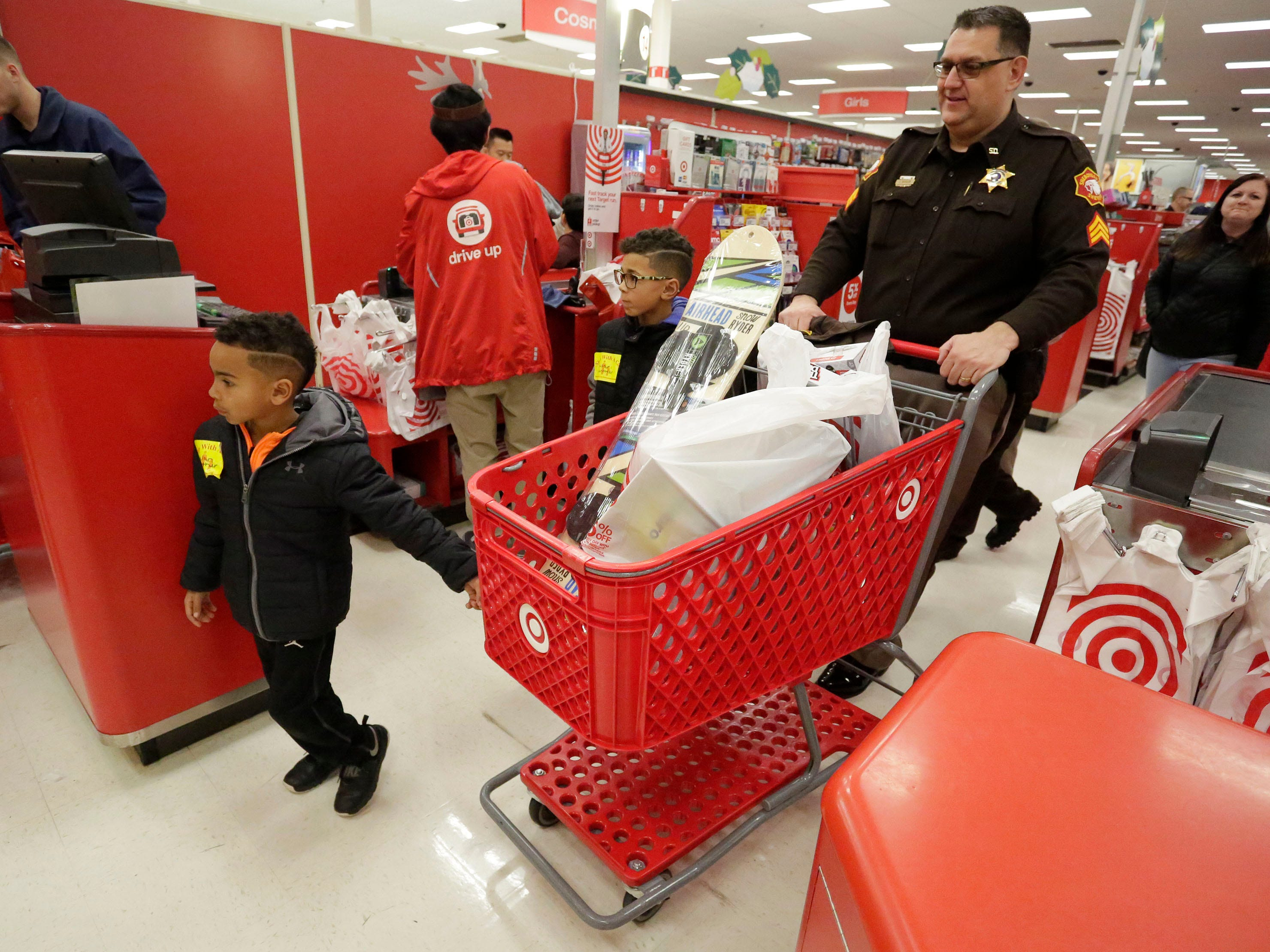 Sheriff Department's Lance Dassler, pushes a cart with youngsters who received toys in the Shop with a Cop program, Tuesday, December 4, 2018, in Kohler, Wis. The program, in its 21st year, raises funds to give children a chance to buy holiday gifts that they otherwise might not receive.