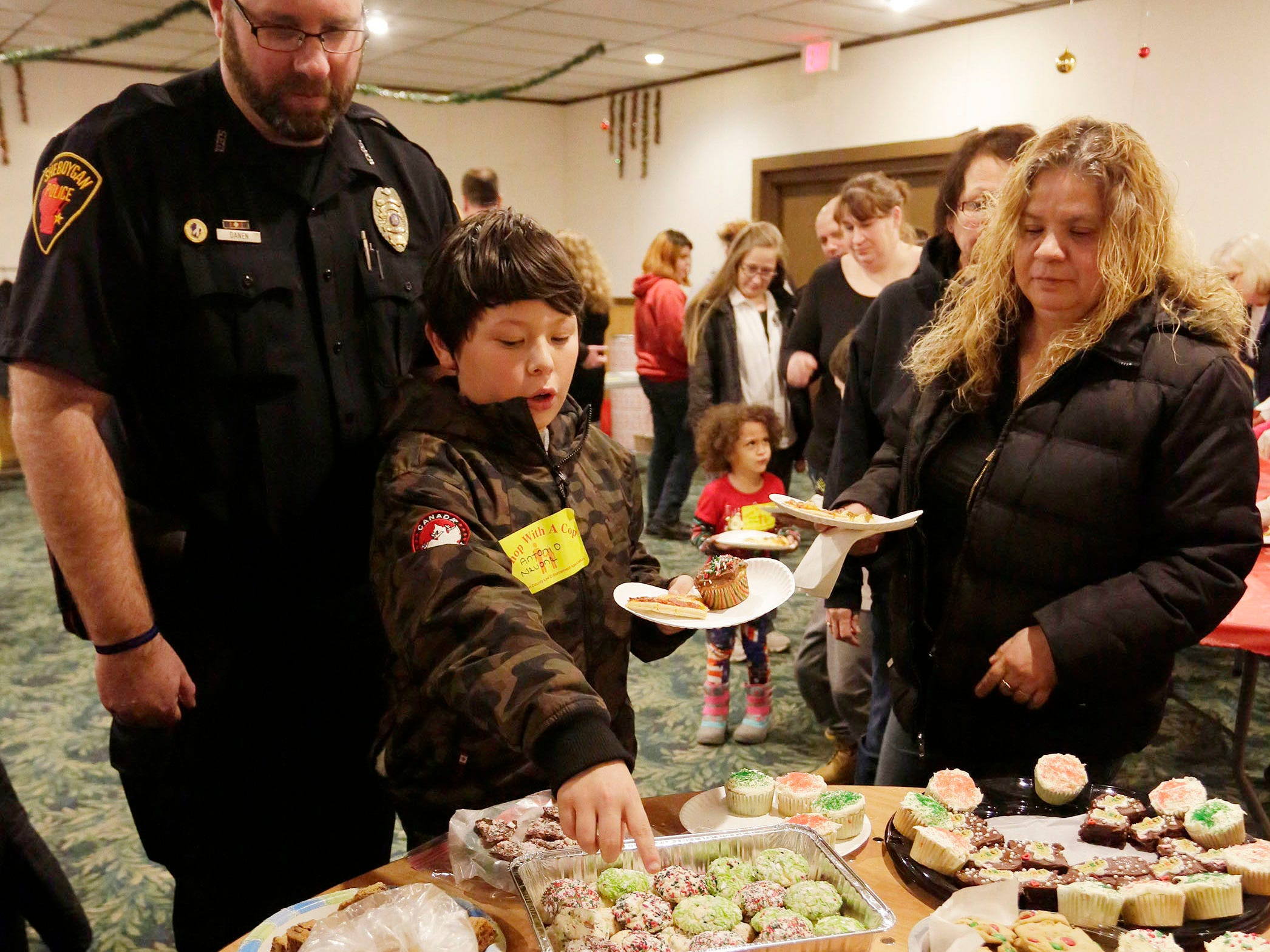 Children and officers had many different types of cookies and holiday treats to eat at Lakeshore Lanes before Shop with Cop, Tuesday, December 4, 2018, in Sheboygan, Wis. The program, in its 21st year, raises funds to give children a chance to buy holiday gifts that they otherwise might not receive.