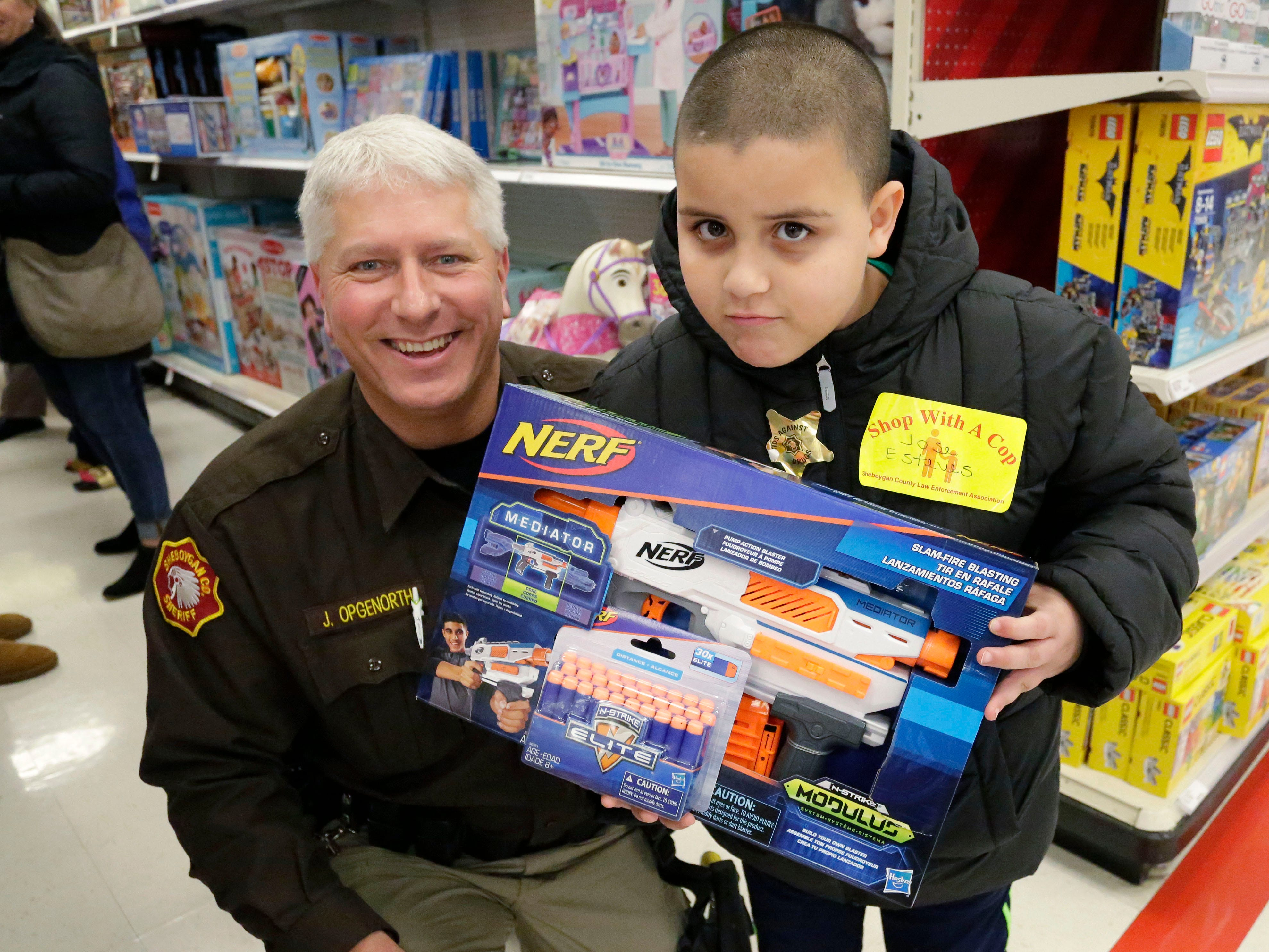 Sheriff Department's Jim Opgenorth, left, poses with Jose Esteves, 8, of Sheboygan, Wis., after selecting a toy during the 21st annual Shop with a cop, Tuesday, December 4, 2018, in Kohler, Wis. The program, in its 21st year, raises funds to give children a chance to buy holiday gifts that they otherwise might not receive.