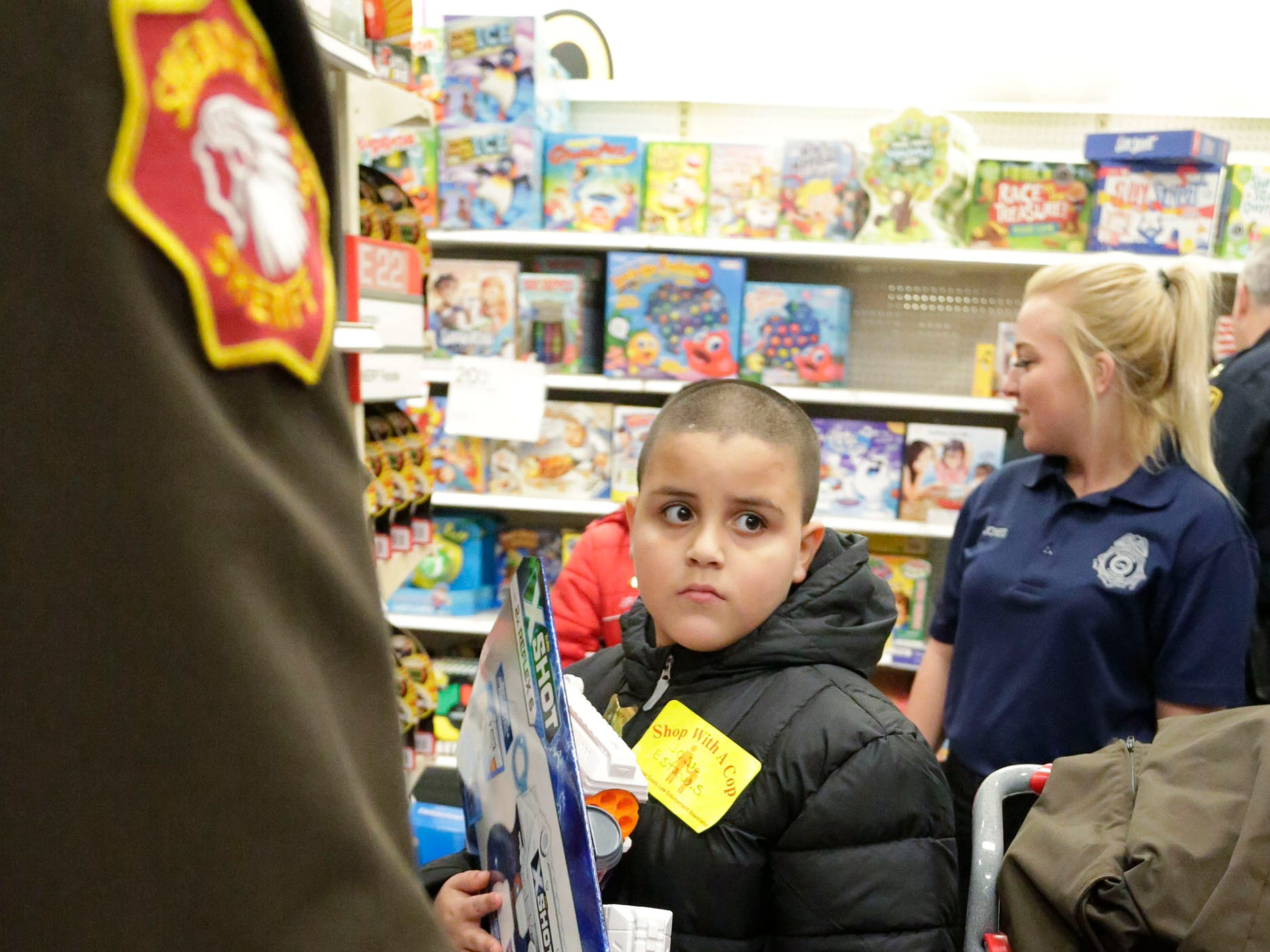 Jose Esteves, 8, of Sheboygan, Wis., holds a toy he selected during Shop with a Copy, Tuesday, December 4, 2018, in Kohler, Wis. The program, in its 21st year, raises funds to give children a chance to buy holiday gifts that they otherwise might not receive.