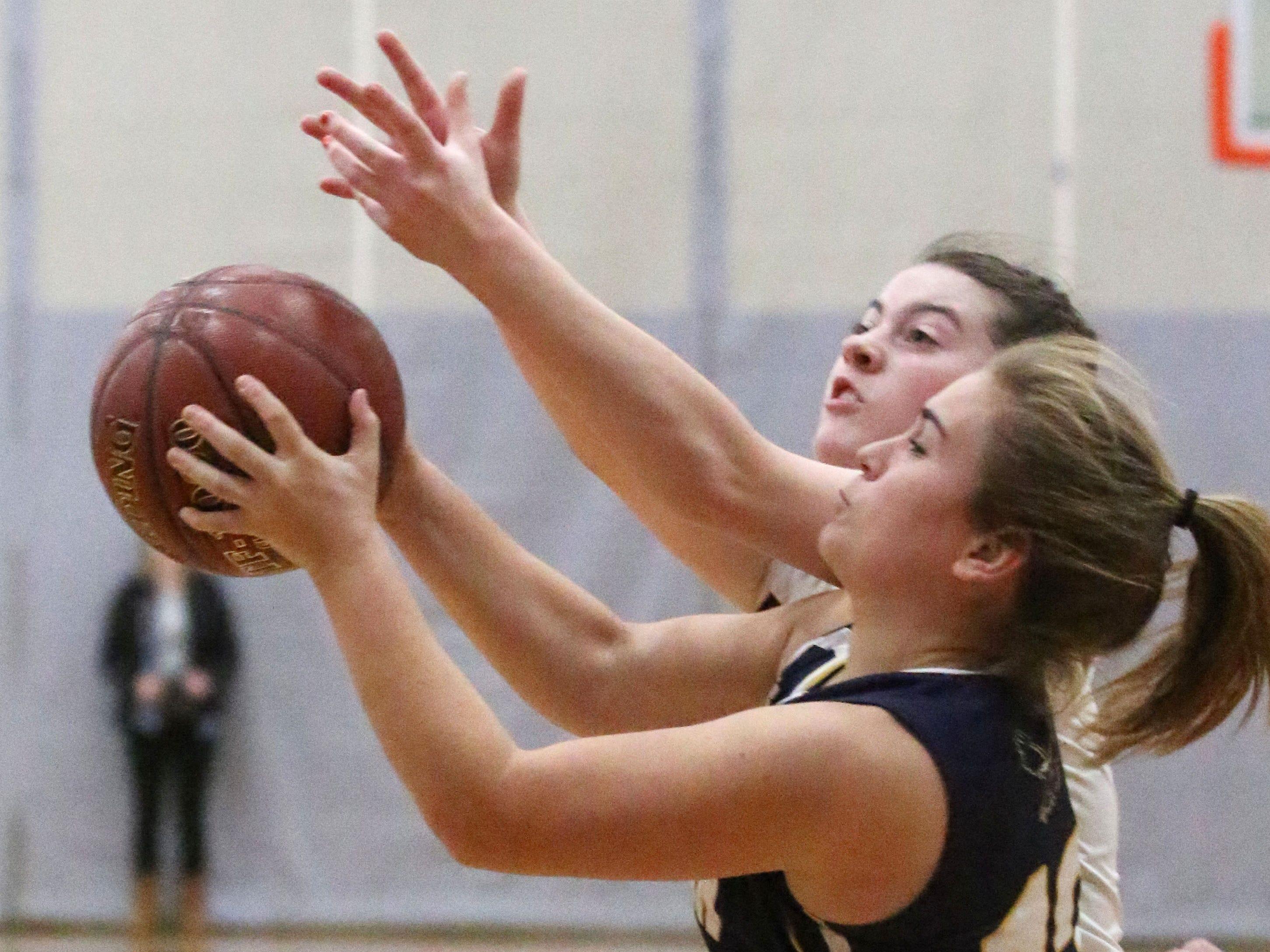 Sheboygan Christian's Megan Moeller (12) rebounds the ball by Cedar Grove-Belgium's Maycie Navis (12), Tuesday, December 4, 2018, in Cedar Grove, Wis.