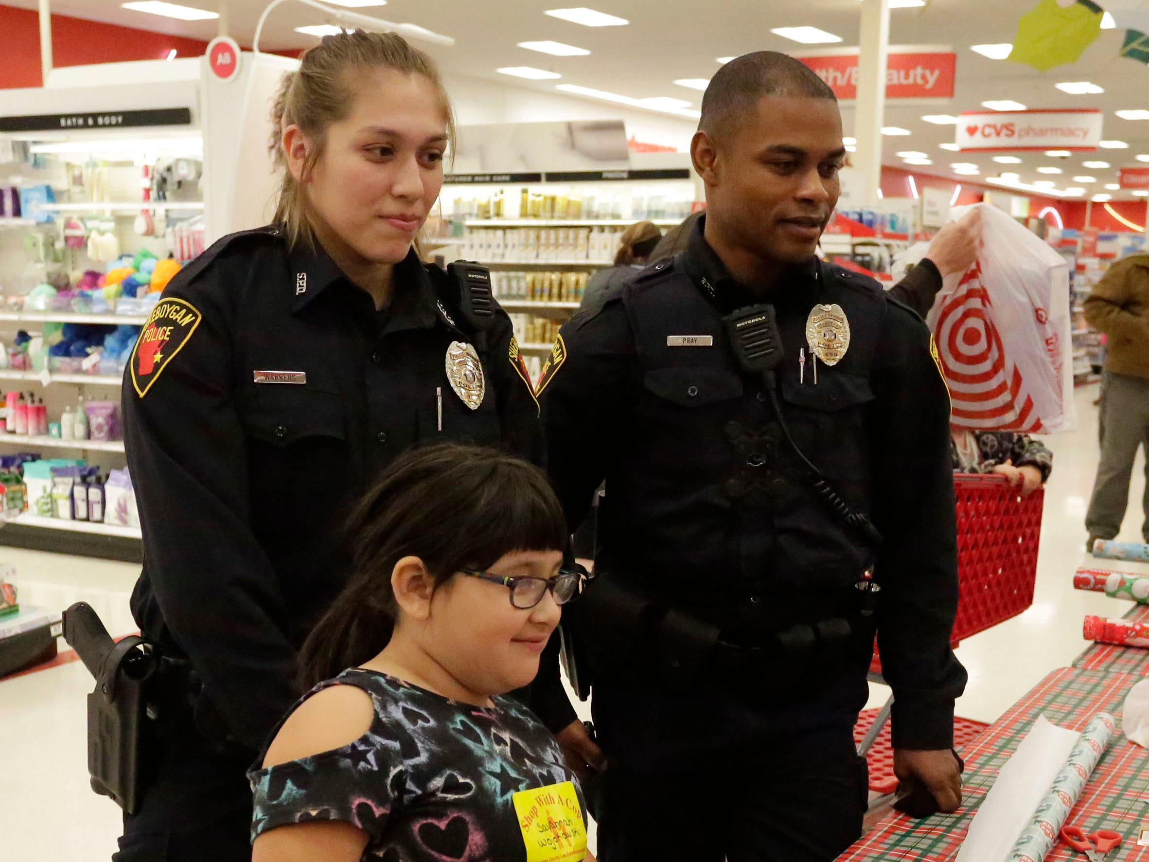 Sheboygan police officers Lina Warrens, left, and Brian Pray wait with Savannah Wojokowski, 9, of Sheboygan, Wis., while she gets a package wrapped during Shop with a Cop at Target, Tuesday, December 4, 2018, in Kohler, Wis. The program, in its 21st year, raises funds to give children a chance to buy holiday gifts that they otherwise might not receive.