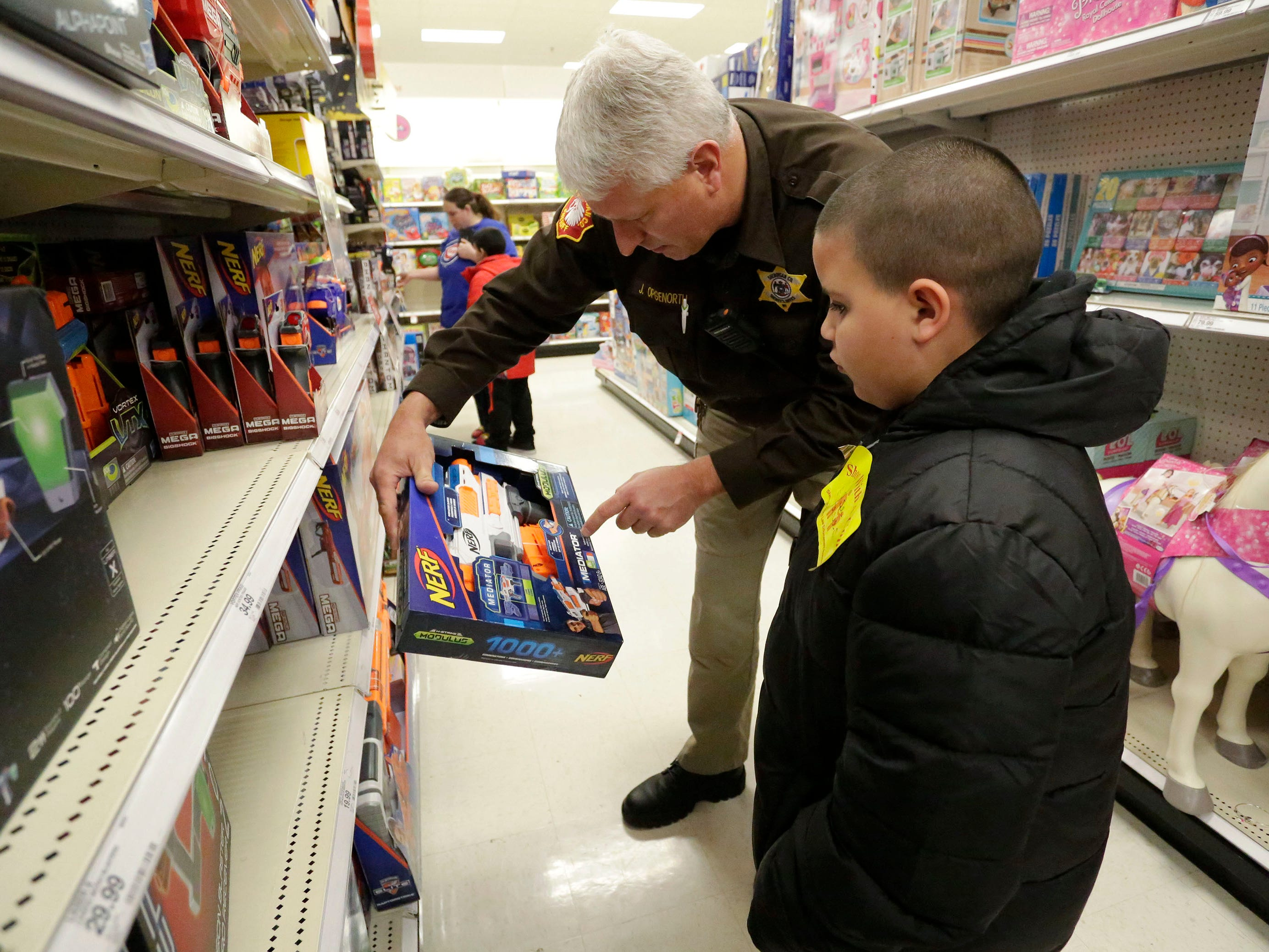 Sheriff Department's Jim Opgenorth, left, points a feature on a toy at Target to Jose Esteves, 8, of Sheboygan, Wis., during the 21st annual Shop with a cop, Tuesday, December 4, 2018, in Kohler, Wis. The program, in its 21st year, raises funds to give children a chance to buy holiday gifts that they otherwise might not receive.