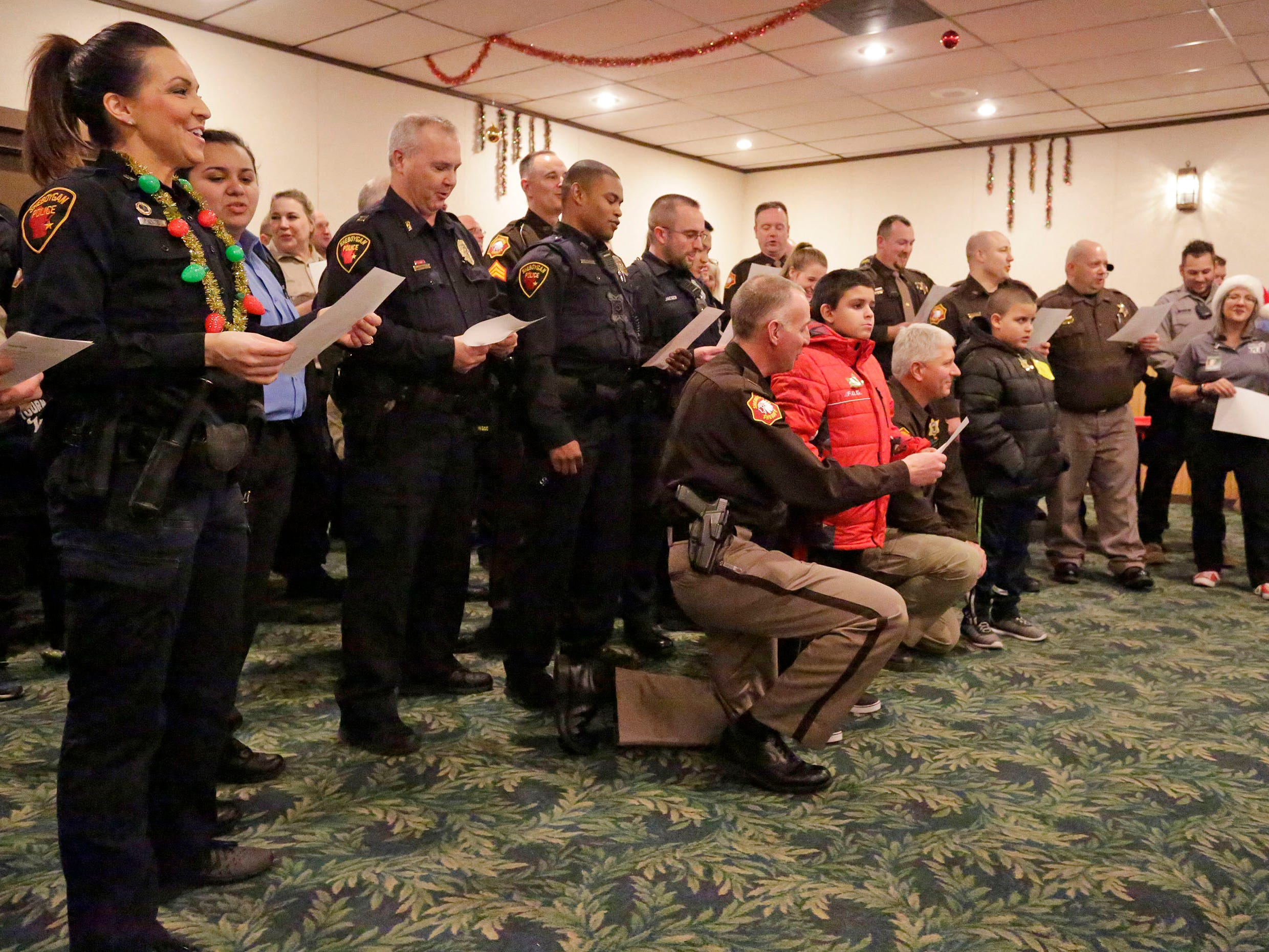 Sheboygan County area law enforcement people sing Christmas carols at Lakeshore Lanes at the start of Shop with a Cop, Tuesday, December 4, 2018, in Sheboygan, Wis.  The program, in its 21st year, raises funds to give children a chance to buy holiday gifts that they otherwise might not receive.