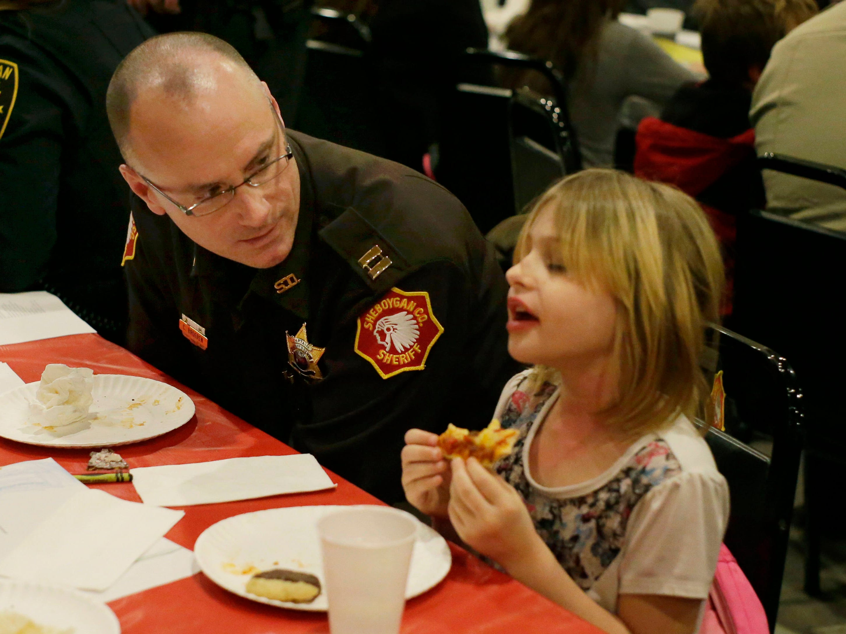 Sheboygan County Sheriff Capt. Chad Broeren, left, listens to Hinata Beckwith, 10, of Sheboygan, talk while at Lakeshore Lanes during the kickoff for Shop with a Cop, Tuesday, December 4, 2018, in Sheboygan, Wis. The program, in its 21st year, raises funds to give children a chance to buy holiday gifts that they otherwise might not receive.