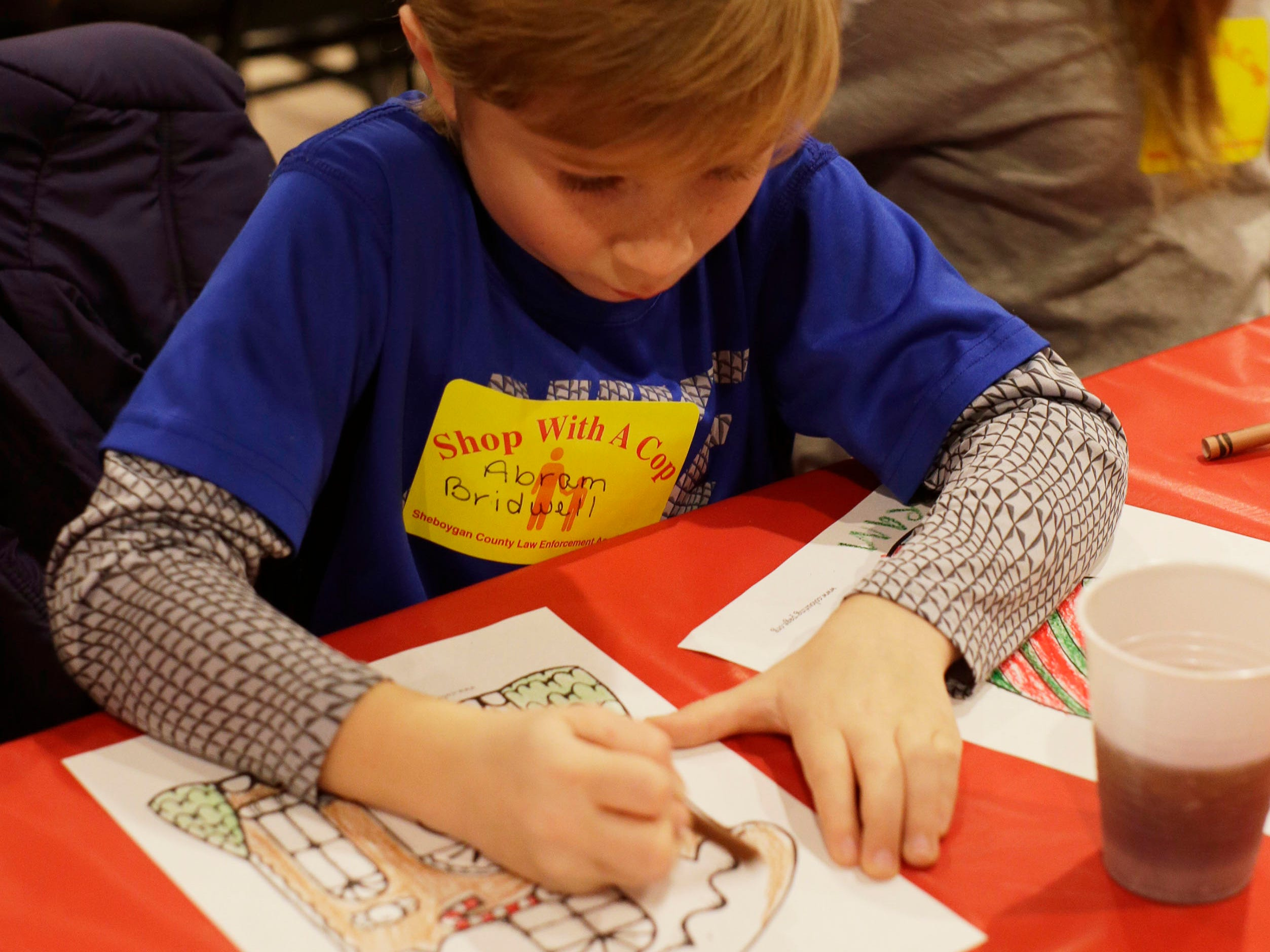 Abram Birdwell, 8, of Plymouth, Wis., colors a picture at Lakeshore Lanes during the start of Shop with a Cop, Tuesday, December 4, 2018, in Sheboygan, Wis. The program, in its 21st year, raises funds to give children a chance to buy holiday gifts that they otherwise might not receive.
