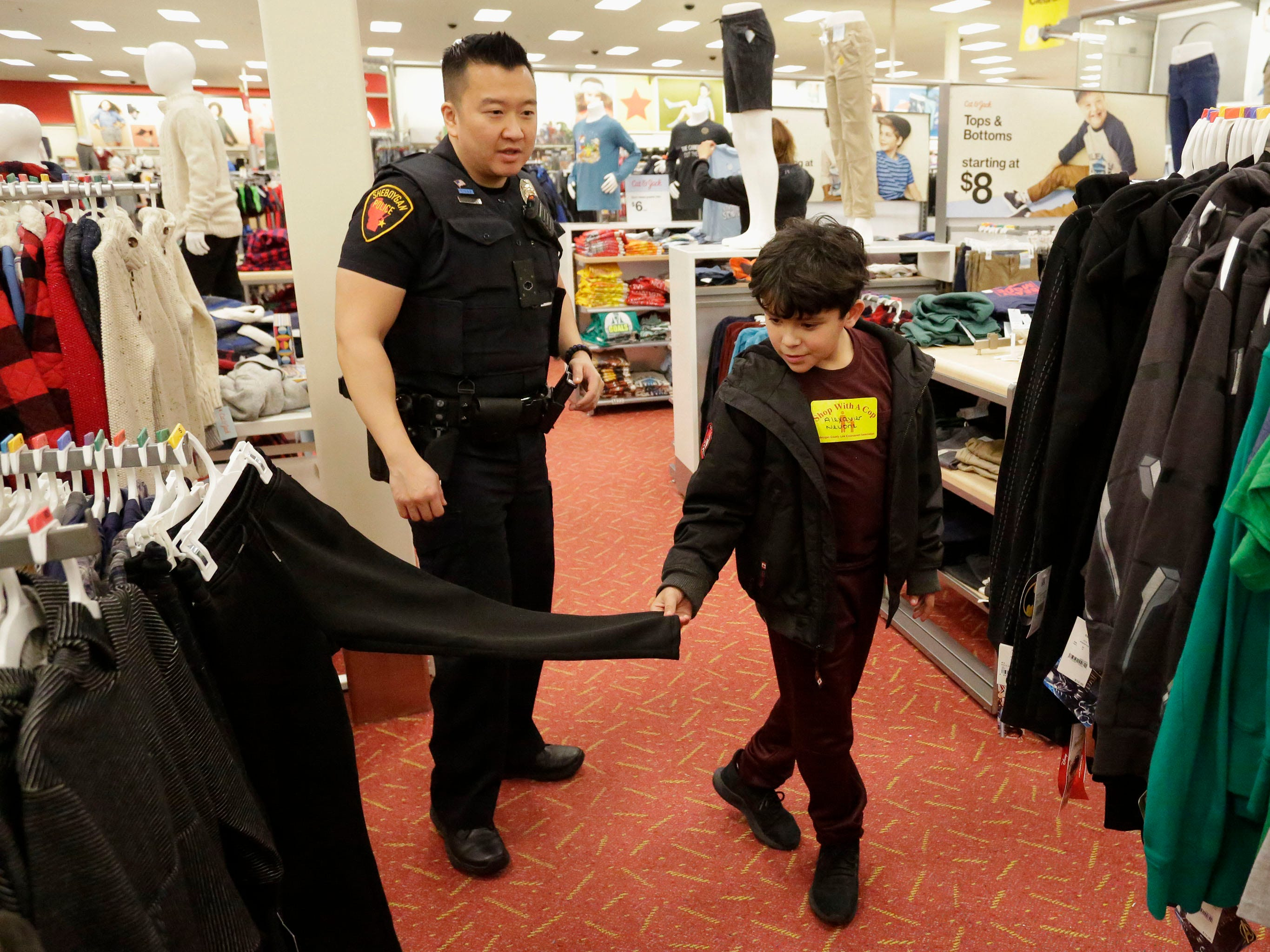 Sheboygan police officer Sung Oetzel, left, helps Alexazier Neuone, 9, of Sheboygan, Wis., pick out clothing during the 21st annual Shop with a Cop at Target, Tuesday, December 4, 2018, in Kohler, Wis. The program, in its 21st year, raises funds to give children a chance to buy holiday gifts that they otherwise might not receive.
