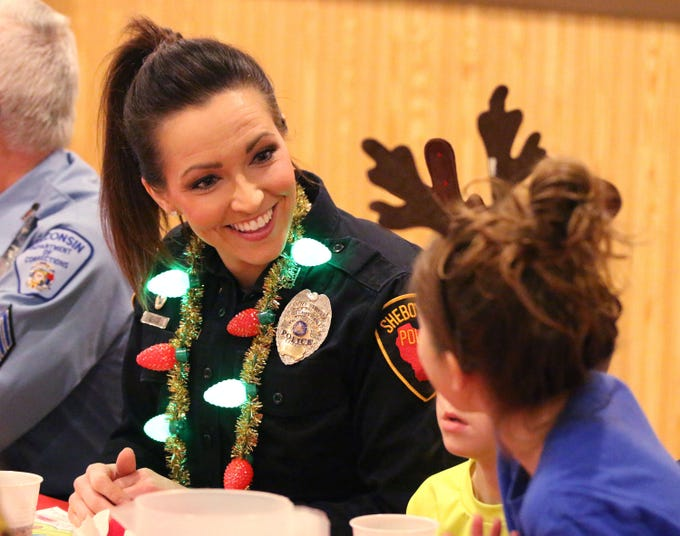 Sheboygan police officer Holly Kehoe smiles as she talks to a participant in the Shop with a Cop program at Lakeshore Lanes, Tuesday, December 4, 2018, in Sheboygan, Wis. The program, in its 21st year, raises funds to give children a chance to buy holiday gifts that they otherwise might not receive.