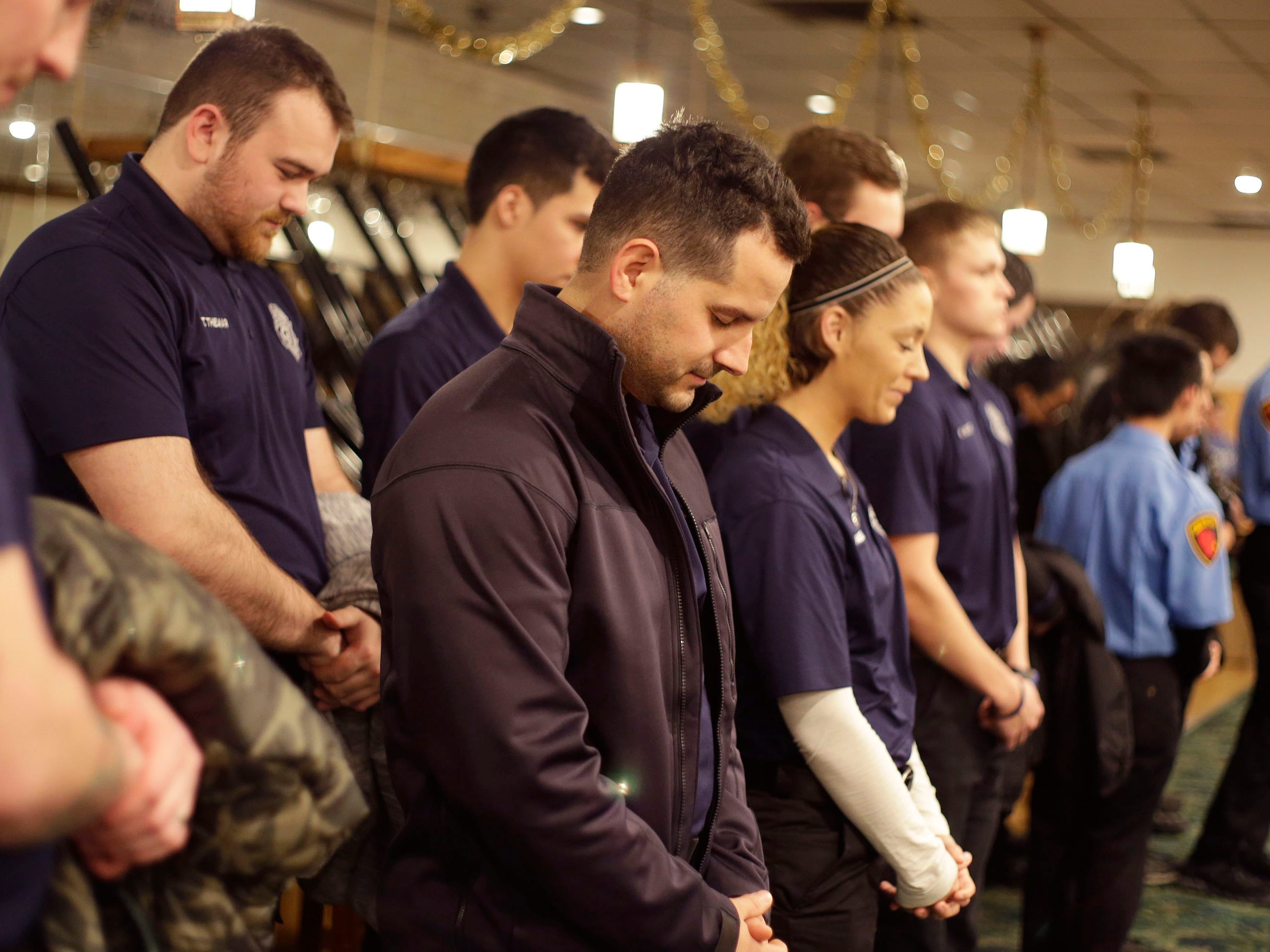 Officers bow their heads in prayer as a police chaplain offers a prayer at the start of the Shop with a Cop program at Lakeshore Lanes, Tuesday, December 4, 2018, in Sheboygan, Wis. The program, in its 21st year, raises funds to give children a chance to buy holiday gifts that they otherwise might not receive.
