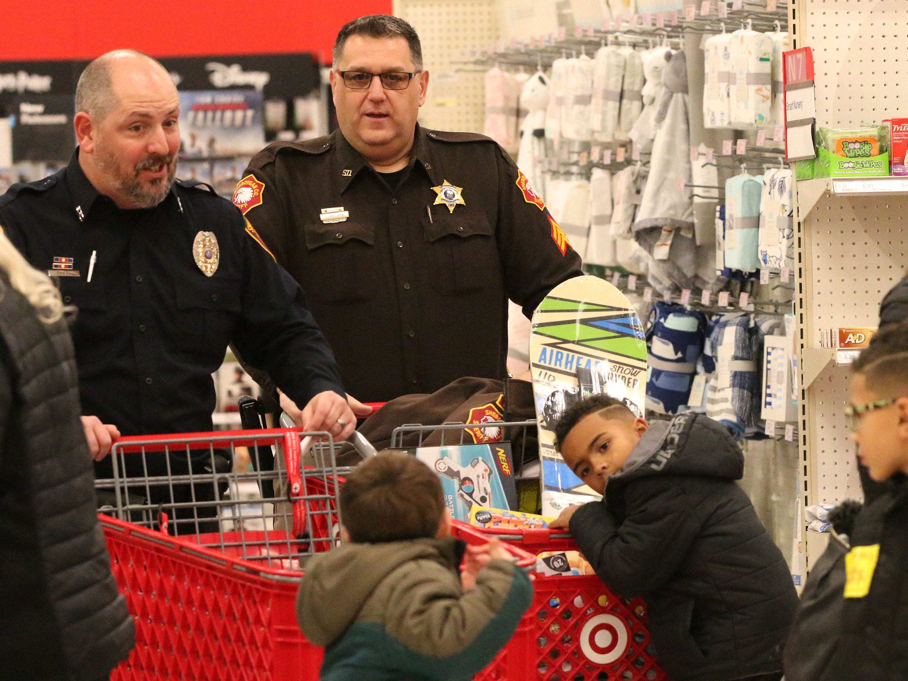 Officers pushed carts and answered questions at Target during Shop with a Cop, Tuesday, December 4, 2018, in Kohler, Wis. The program, in its 21st year, raises funds to give children a chance to buy holiday gifts that they otherwise might not receive.