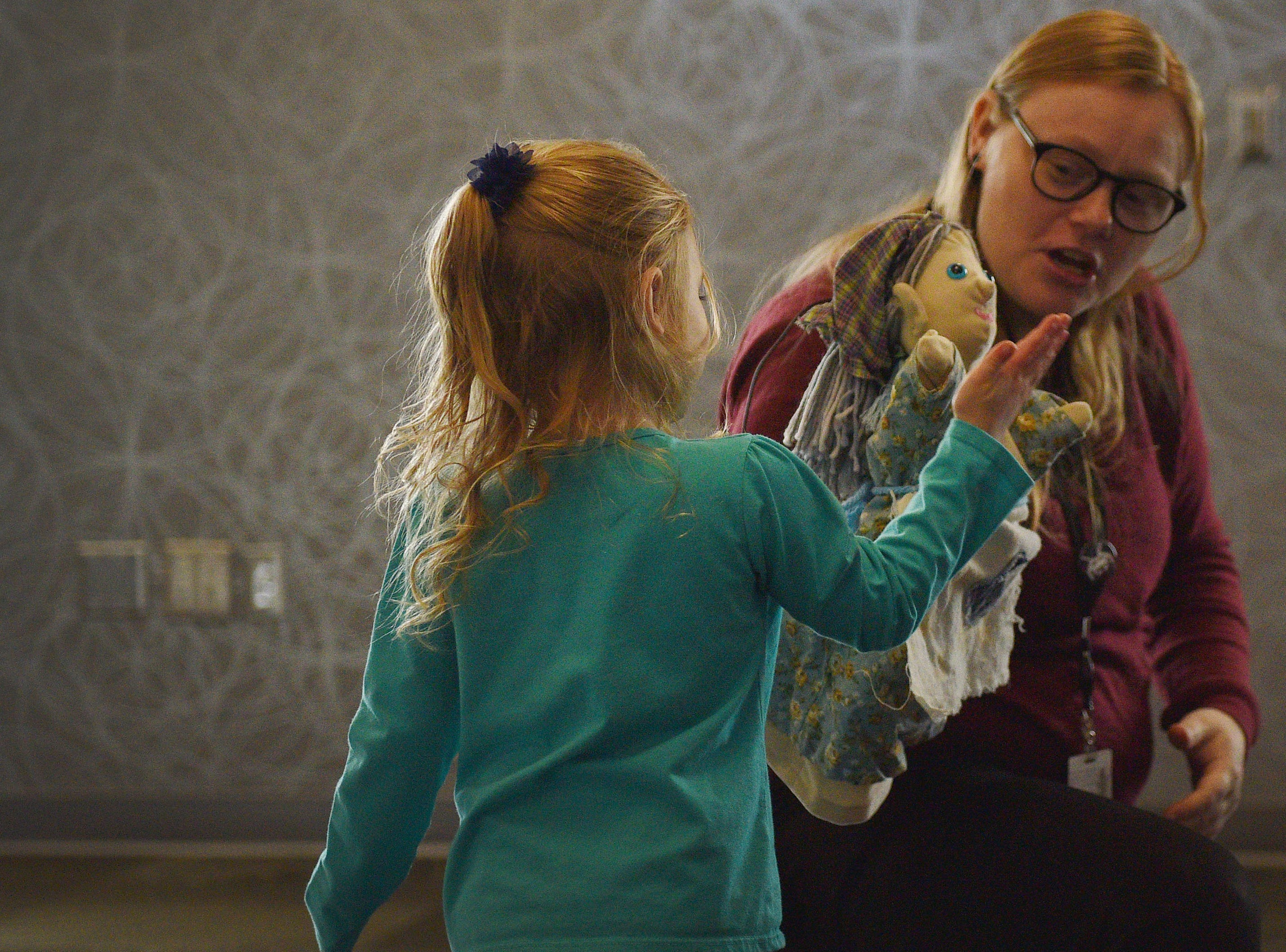 Evelyn Hoesing goes up to Library Associate Amanda Bremmon to high five the puppet from The Christmas Gift puppet show at the Prairie West Branch Wednesday, Dec. 5, in Sioux Falls.