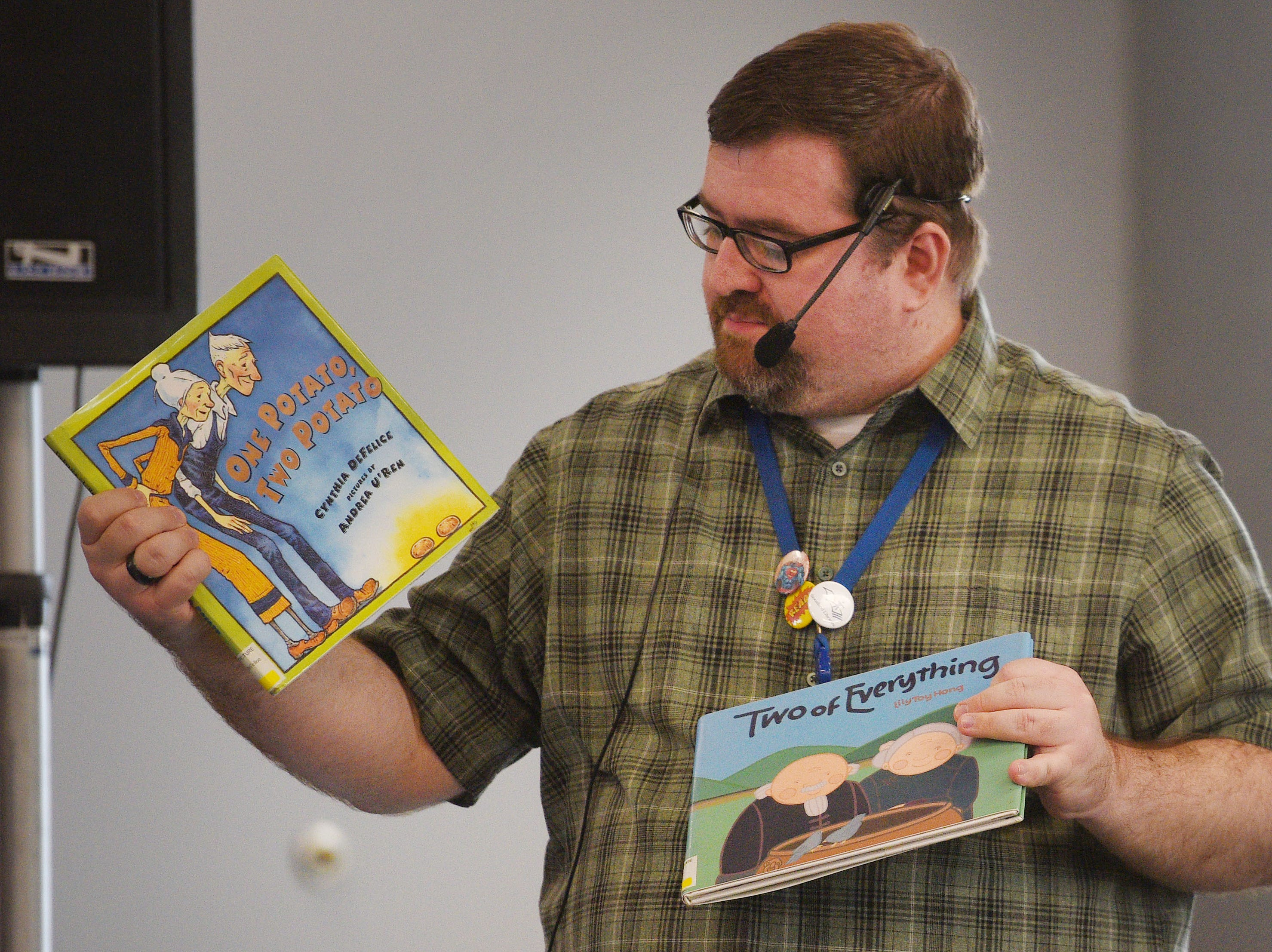 Library Associate Brian Borden introduces the books he is going to perform during The Christmas Gift puppet show at the Prairie West Branch Wednesday, Dec. 5, in Sioux Falls.
