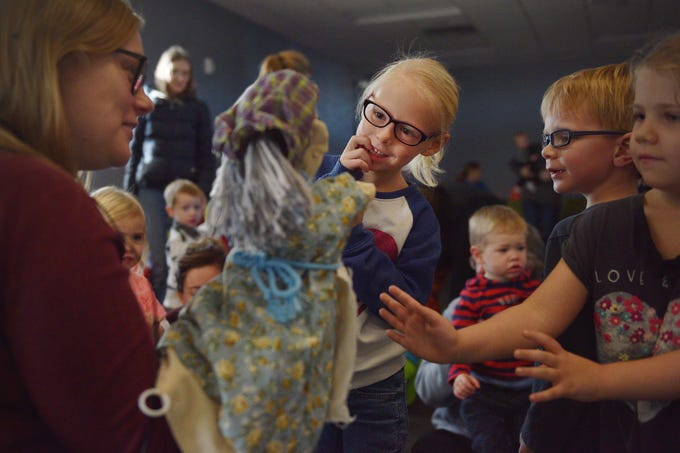 Eden Johnson, center, looks at a puppet after a performance of The Christmas Gift puppet show at the Prairie West Branch Wednesday, Dec. 5, in Sioux Falls. Library Associate Amanda Bremmon, far left, invited the kids to come and say hello to the puppets after the show.
