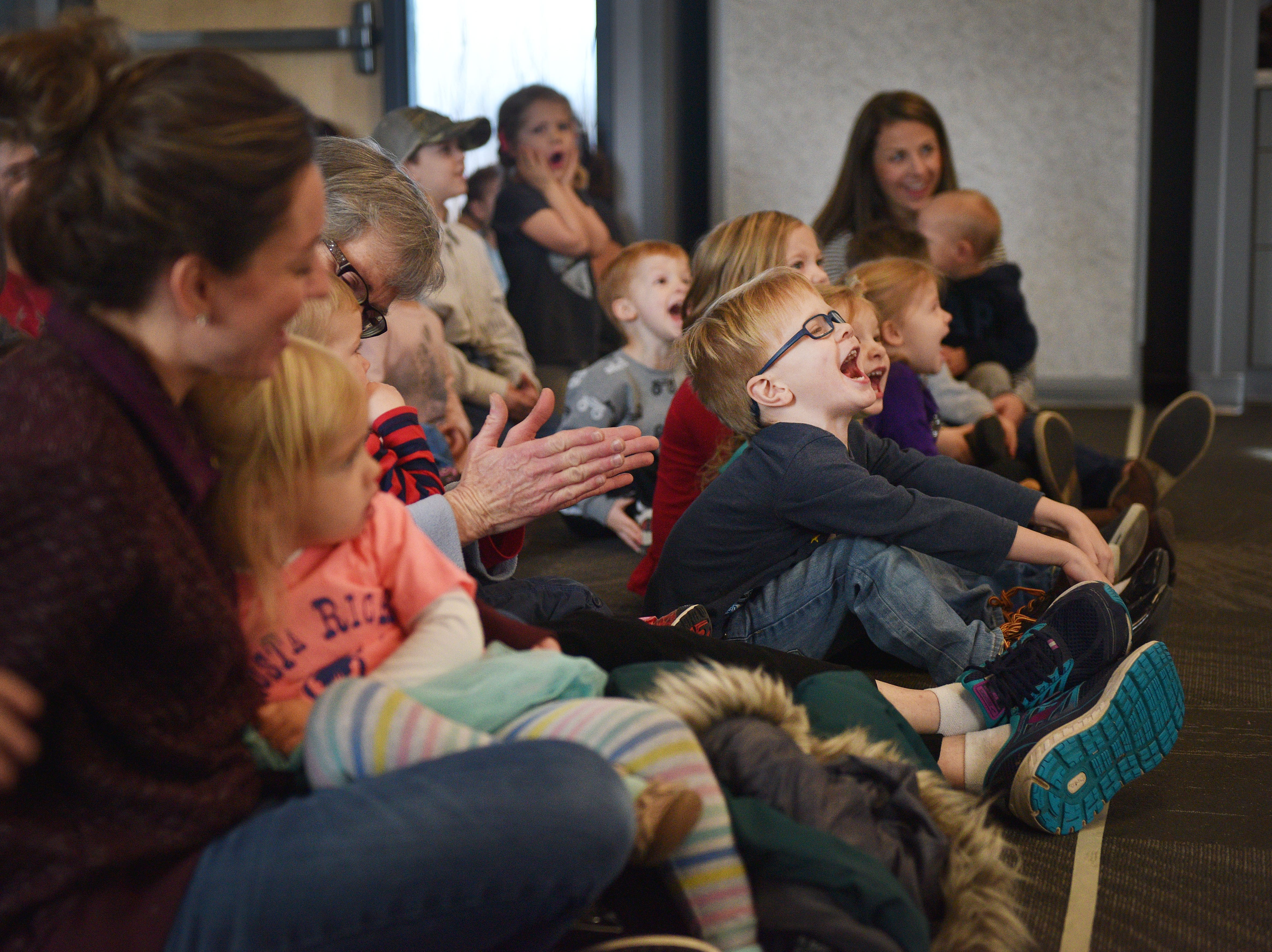 Gavin Dewit, center, cheers for The Christmas Gift puppet show at the Prairie West Branch Wednesday, Dec. 5, in Sioux Falls.
