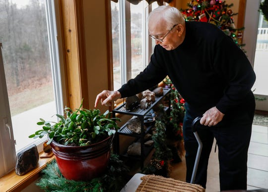Ernie Cooper, who has Alzheimer's, looks at one of the plants inside his home in Branson West on Tuesday, Dec. 5, 2018.
