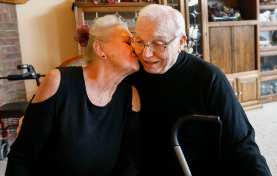Alberta Cooper gives her husband Ernie Cooper, a kiss on the cheek in their living room on Tuesday, Dec. 5, 2018. Alberta is caring for Ernie, who has Alzheimer's.