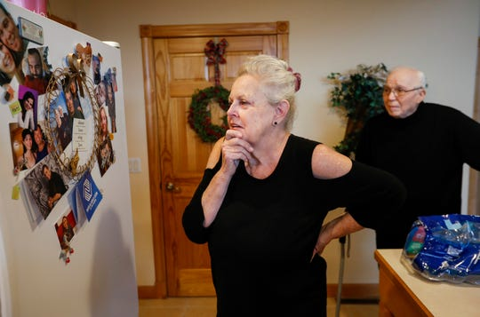 Alberta Cooper looks at photographs of her family as her husband Ernie walks up behind her on Tuesday, Dec. 5, 2018. Alberta is caring for Ernie who has Alzheimers.