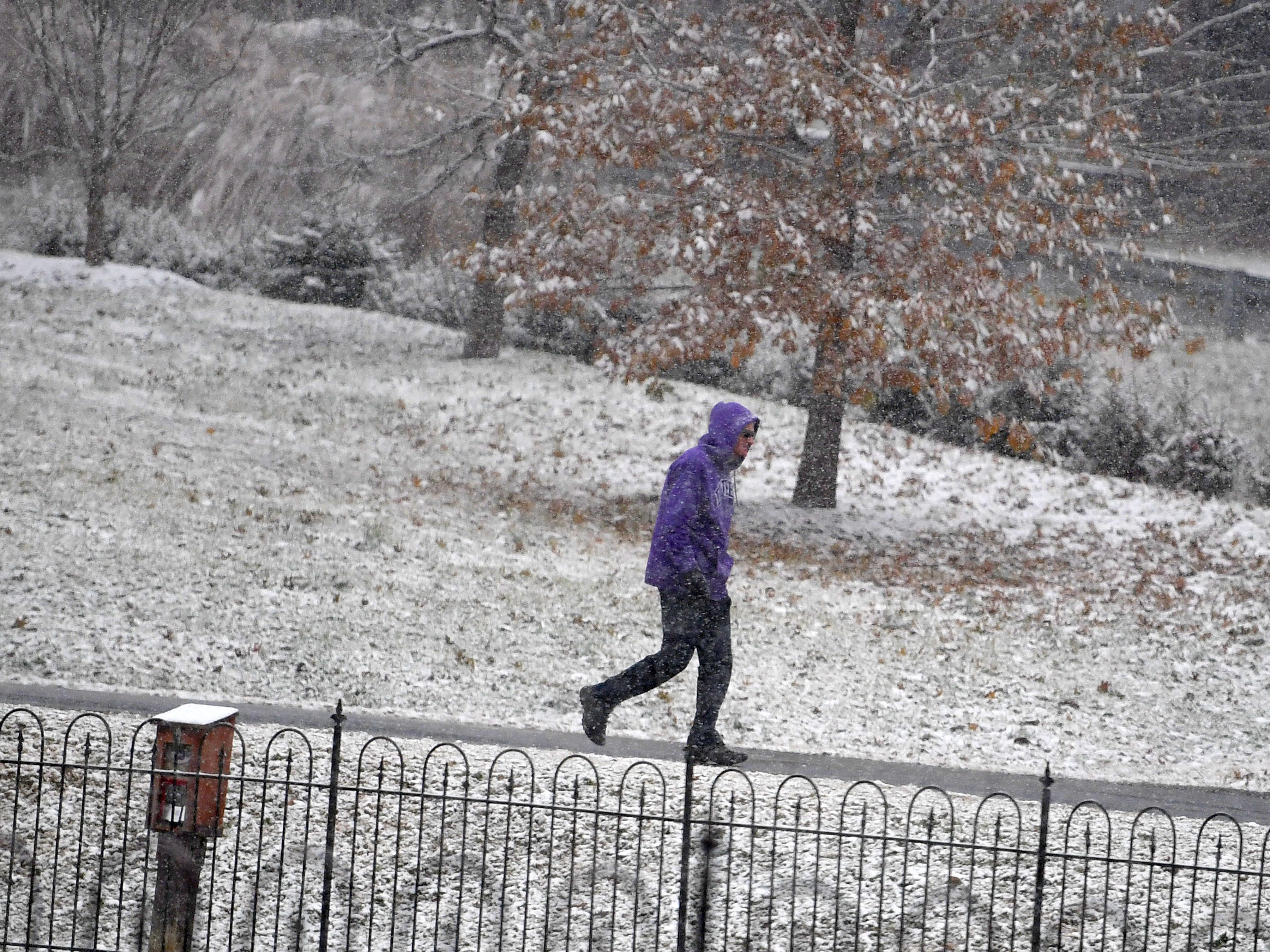 A pedestrian walks around Gypsy Hill Park in the falling snow in Staunton on Wednesday, Dec. 5, 2018.