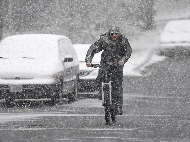 Snow falls as a bicyclist makes his way along Caroline Street in Staunton on Wednesday, Dec. 5, 2018.