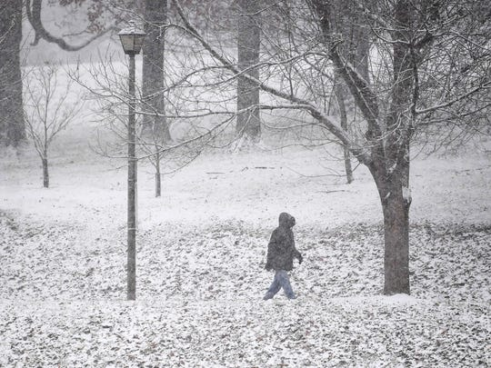 Snow falls around Kayla Prather of Staunton as she walks through it while walking at Gypsy Hill Park in Staunton on Wednesday, Dec. 5, 2018.