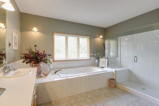 The master en suite has been remodeled and features a large walk-in glass shower and separate soaking tub.