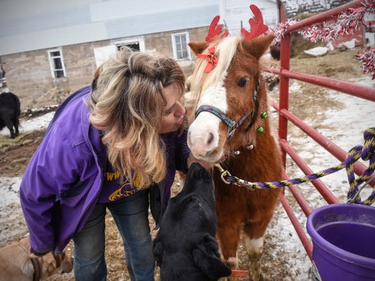 Joah's Ark owner Jo Olson kisses Gum Drop Wednesday, Dec. 5, at her farm near St. Augusta.