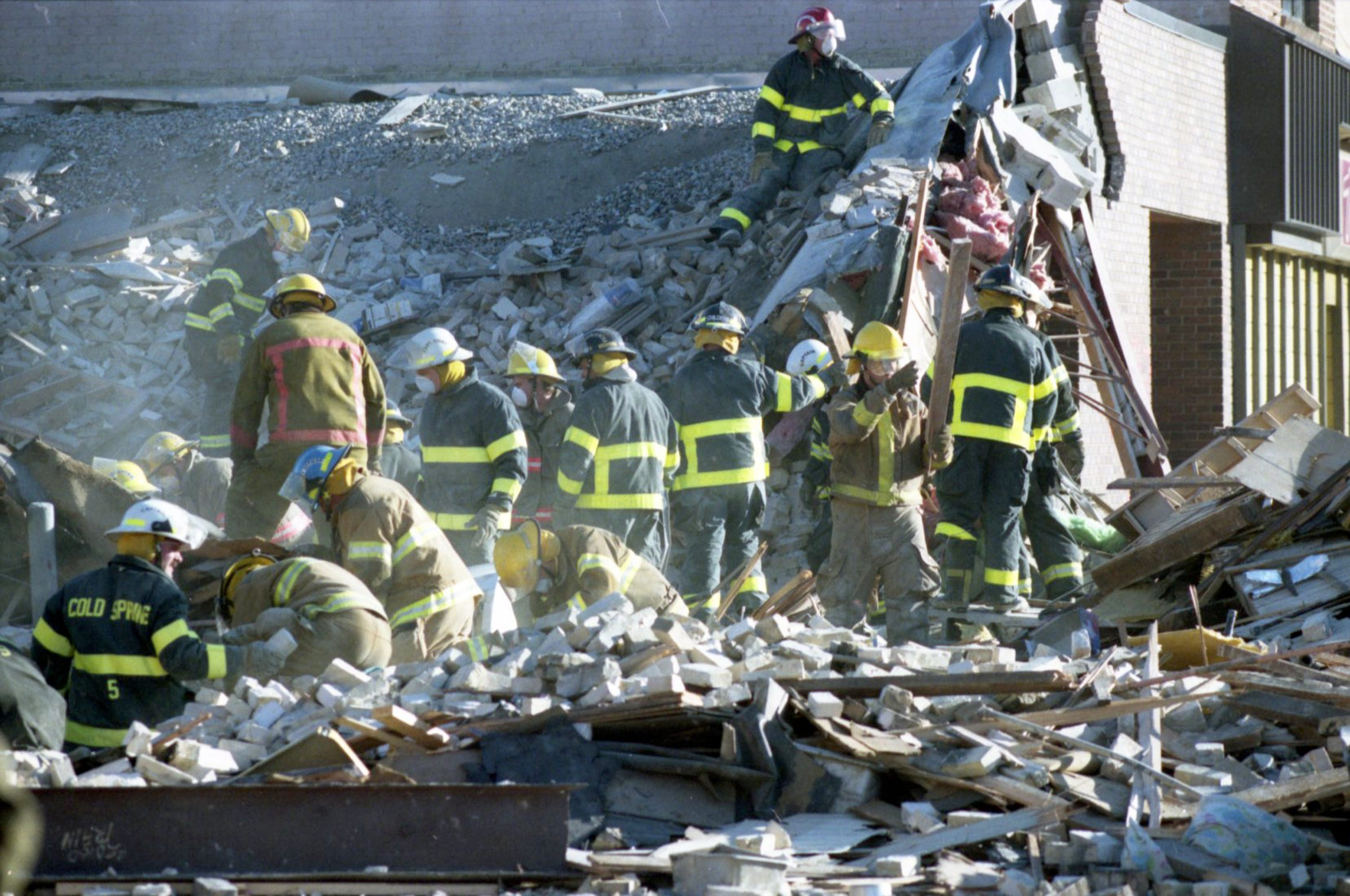 Firefighters from five surrounding departments comb through the rubble of Bellantti's Pizza & Deli building Dec. 11 after a fatal gas main explosion leveled the building and heavily damaged adjacent structures.