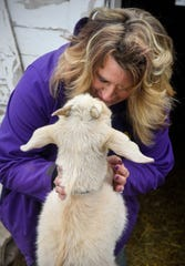 Joah's Ark owner Jo Olson snuggles with one of her goats  Wednesday, Dec. 5, at her farm near St. Augusta.