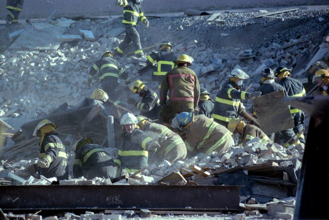 Firefighters comb through the rubble of Bellantti's Pizza & Deli building Dec. 11 after a fatal gas main explosion leveled the building and heavily damaged adjacent structures.