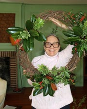 Garden Club member Gail Hill shows off a wreath she created. Photo by Betsy Kellenberger.