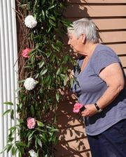 Volunteer Ann Moland decorates the front doorway of the Maclay House.