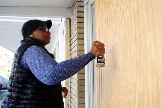 "Executive Director and Founder of Legacy School of Performing Arts Institute, Inc. spray paints ""closed"" on boards covering the windows at the school Quincy Tuesday, Dec. 4, 2018, after it was damaged by Hurricane Michael in October."