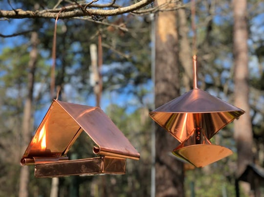 Copper bird feeders are both functional and ornamental.