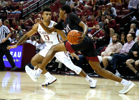 Dec 3, 2018; Tallahassee, FL, USA; Troy Trojans forward Javan Johnson (1) moves the ball abasing Florida State Seminoles guard Anthony Polite (13) at Donald L. Tucker Center during the first half. Mandatory Credit: Glenn Beil-USA TODAY Sports