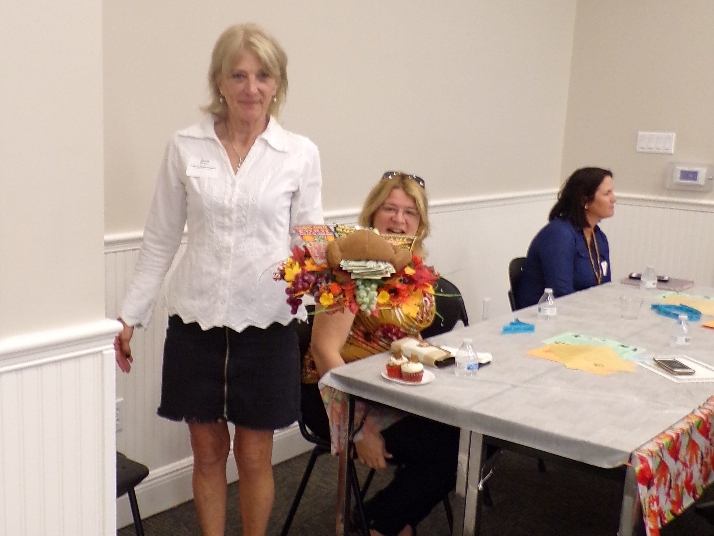 """Sandi Morgan with Coldwell Banker Paradise carrying Caliber Home Loans' """"Money, Money, Money"""" cake."""