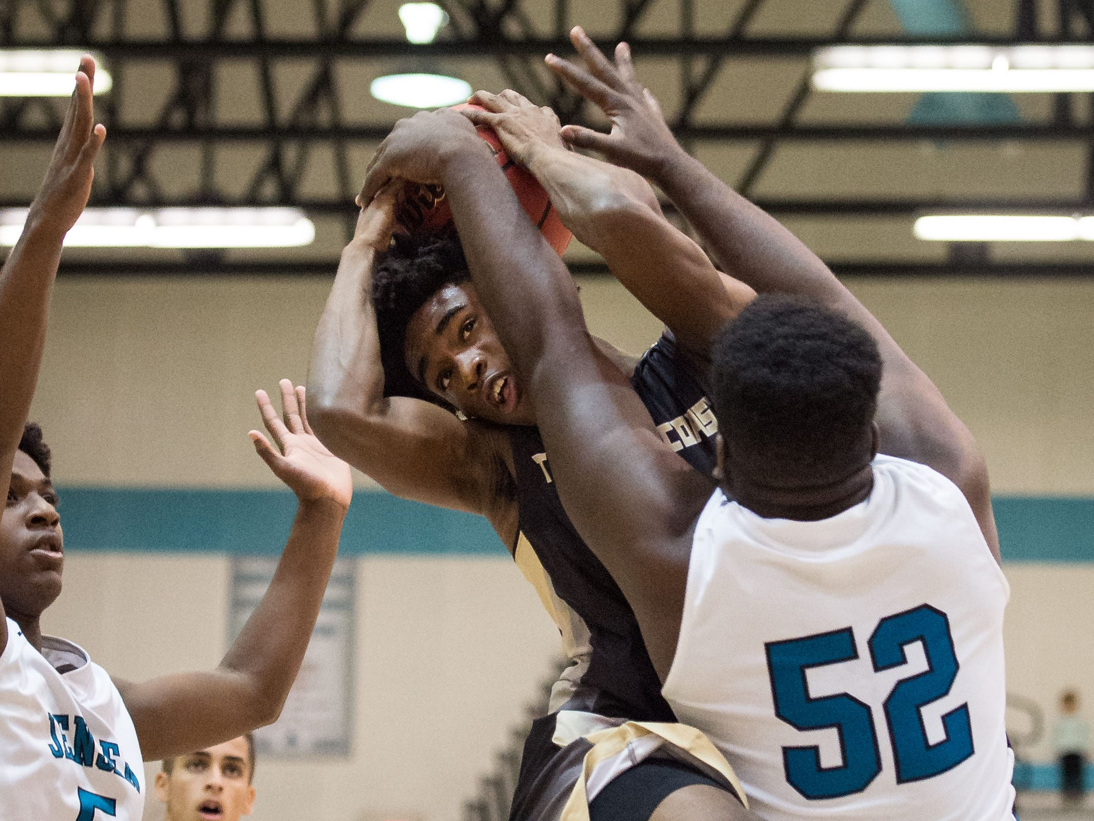 Treasure Coast's Nemuel Robinson (center) is stopped up by Jensen Beach's Emanuel Rogers during the first period of the high school boys basketball game Tuesday, Dec. 4, 2018, at Jensen Beach High School.