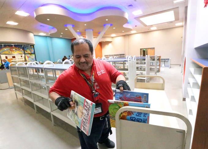 Joe Dominguez, information specialist with the El Paso Public Library begins the process of stacking books inside the expanded Kids Zone in the Richard Burges Library at 9600 Dyer Wednesday. The lights on the ceiling structure in background changes color.  The library is being remodeled and expanded with a $1.4 million investment from the 2012 Quality of Life Bond program. The 24,000 square foot library will include an expanded computer lab, an additional study room, expanded community meeting room space and self serve book check out stations.