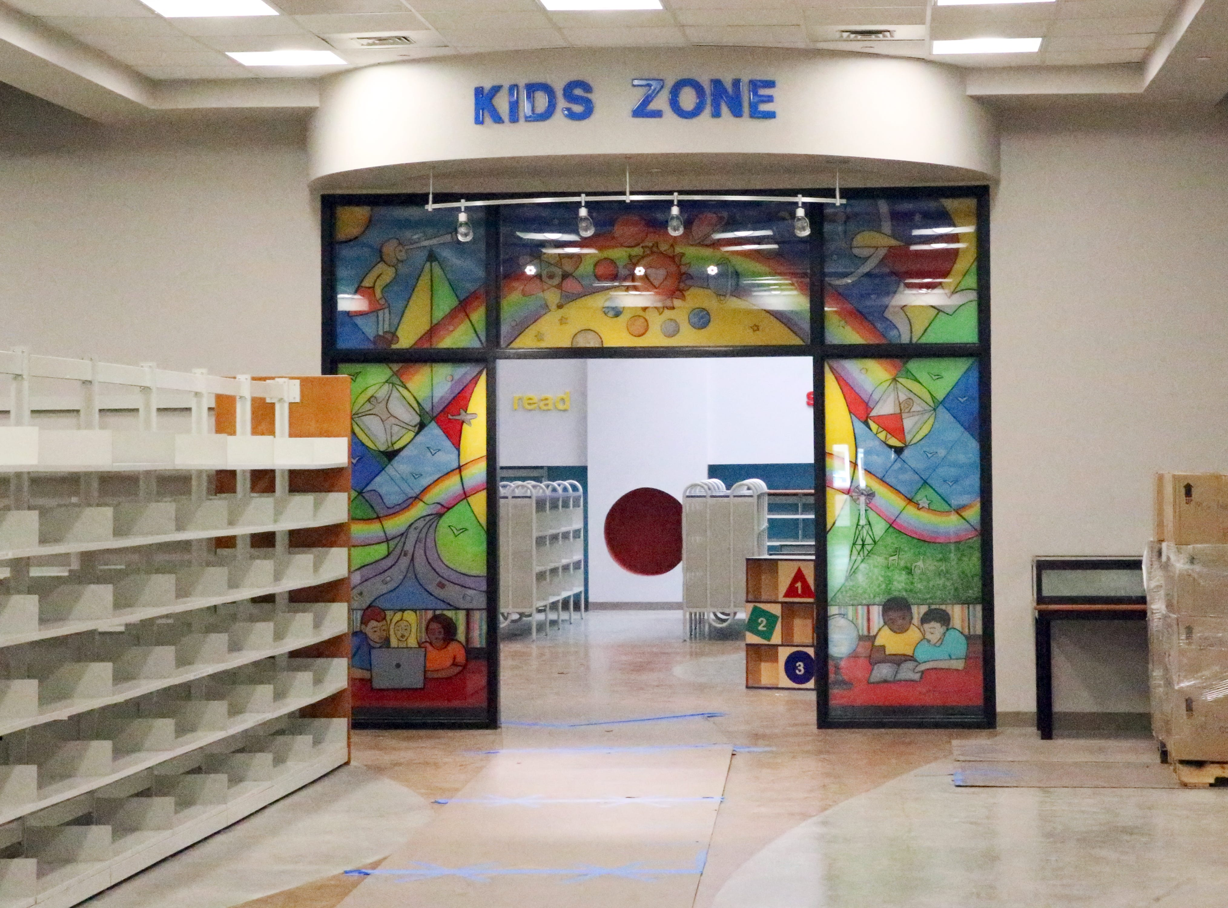 The newly expanded Kids Zone features art glass panels from El Paso artist Hal Marcus at the entrance. Boxes at right contain part of 72,000 books awaiting shelving.