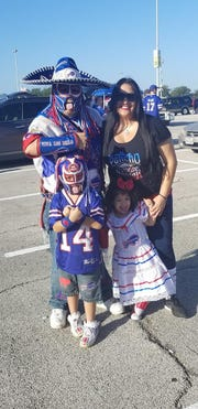 Ezra Castro poses with his family outside NRG stadium before a game between the Buffalo Bills and the Houston Texans.