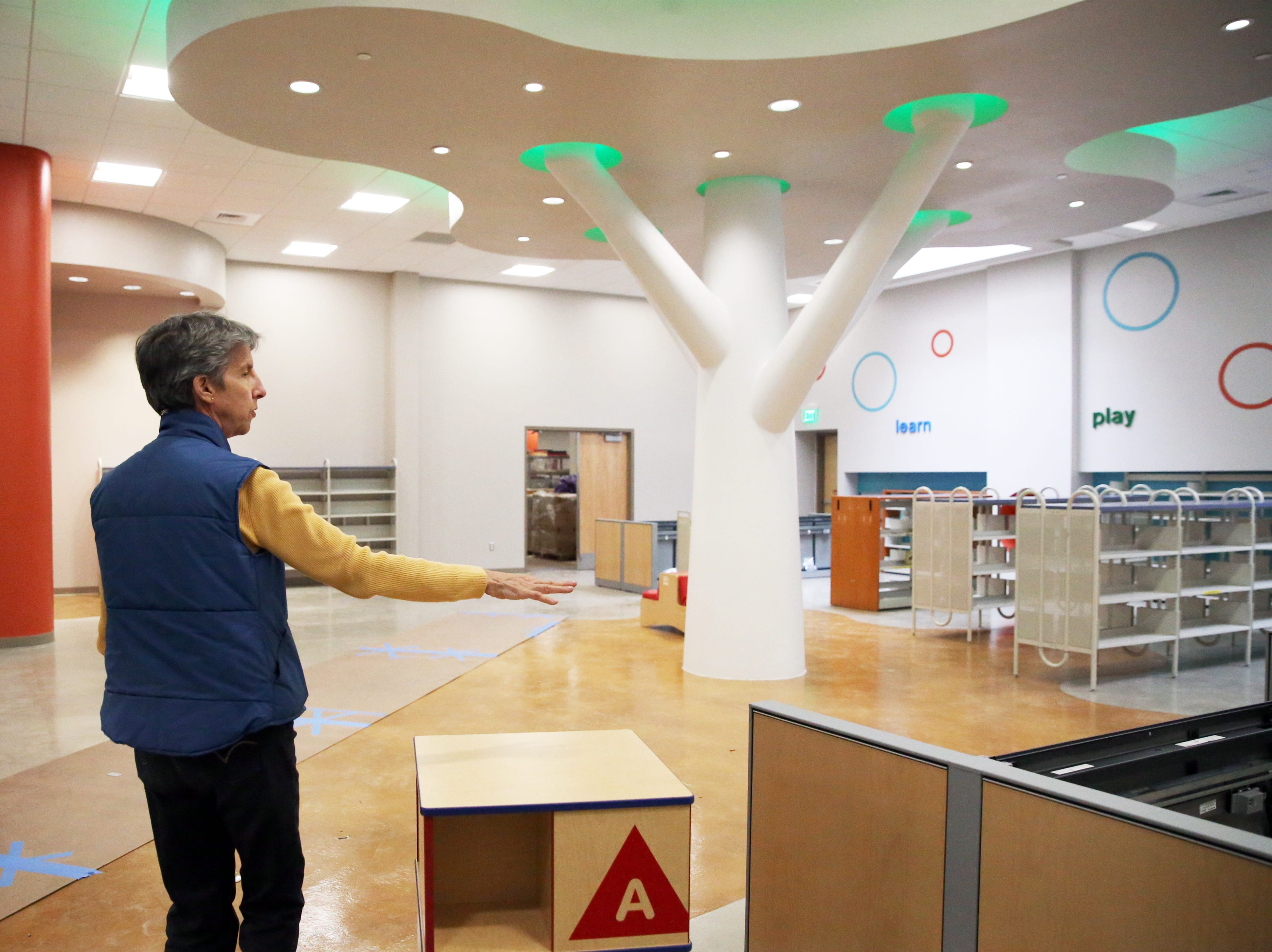 Ellen Eyberg, regional library branch manager gives a tour inside the expanded Kids Zone area of the newly renovated Richard Burges Library branch at 9600 Dyer Street Wednesday.