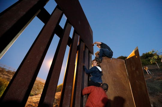 Central American migrants planning to surrender to U.S. border guards climb over the U.S. border wall from Playas de Tijuana, Mexico, late Monday. Thousands of Central American migrants who traveled with recent caravans want to seek asylum in the U.S. but face a decision between crossing illegally or waiting months.
