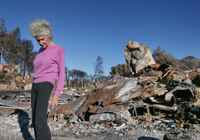 Marsha Maus stands in front of what is left of her mobile home that was destroyed during the Woolsey Fire. Her home in the Seminole Springs Mobile Home Park was among many that burned in the recent fire.