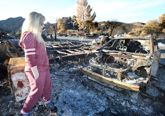 Rosanna DeVere stands in front of the burned-out shell of her 2017 Subaru Outback.  Her home in the Seminole Springs Mobile Home Park in Agoura Hills was destroyed during the Woolsey Fire.
